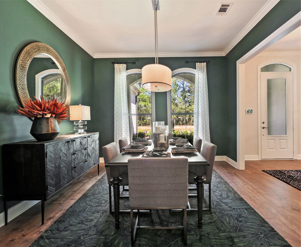 Single family home dining room merchandised with dark green walls and dark wood furnishings in Louisiana.