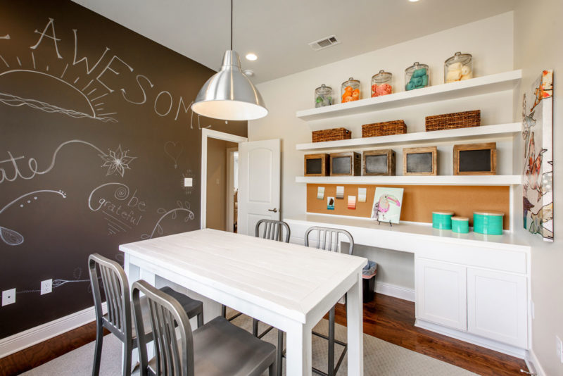 Louisiana model home with whimsically designed craft room including chalkboard wall and build in storage.