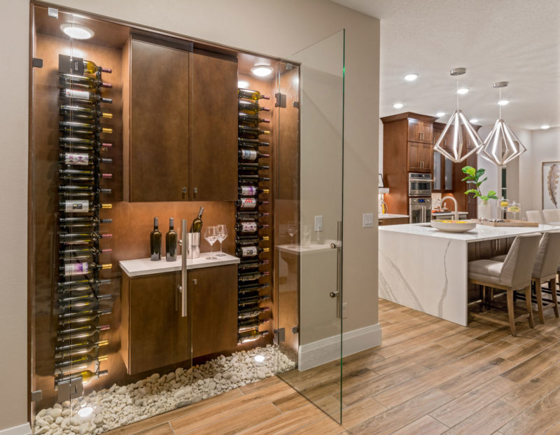 Creative wine storage in wall nook off kitchen in award-winning 55+ home buyer model home in Orlando, Florida.