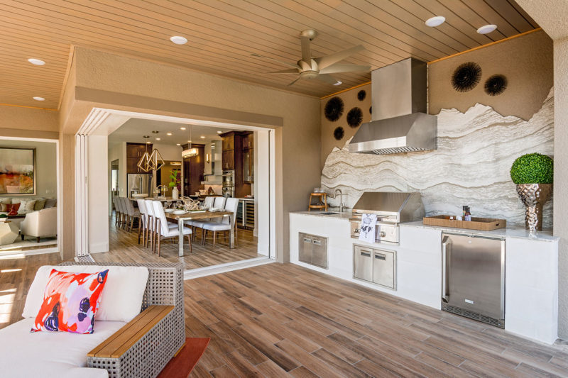 Outdoor kitchen with unique marble piece for backsplash, hardwood outdoor flooring, and lounge chairs in Florida.