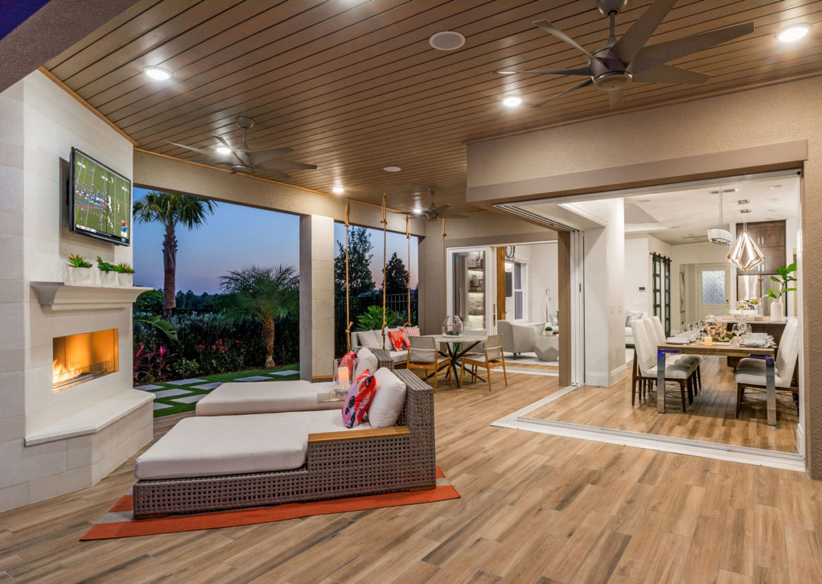 Award winning outdoor living space with lounge chairs, fireplace and open doors into home dining and living room in Florida.