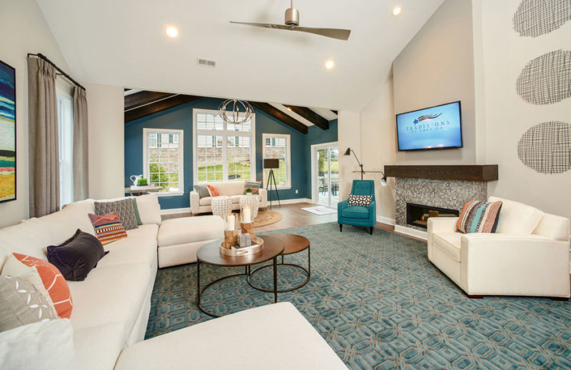 Large high ceiling living room merchandised with white furniture, blue accents and a large tiled fireplace in Pennsylvania.