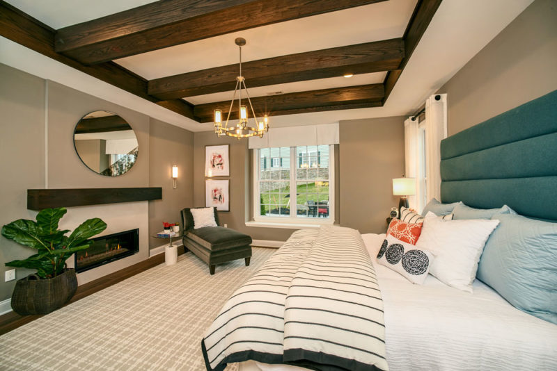 Neutral styled master suite with dark wooden ceiling beams, modern fireplace, and a plush blue headboard in Pennsylvania.