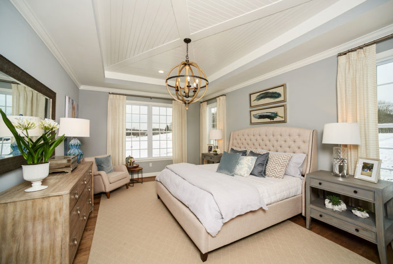 Sophisticated farmhouse master bedroom with tan furnishing, light blue walls and a white wood plank ceiling in Pennsylvania