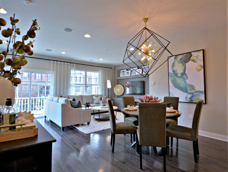 Townhome living and dining area designed with neutral finishes and a large black geometric chandelier in Pennsylvania.
