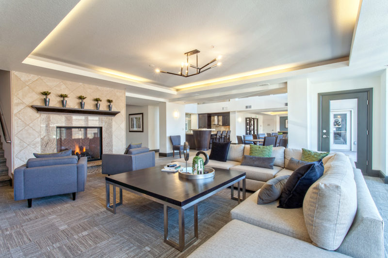 Multifamily community amenity space with travertine fireplace, large cream sectional couch, and accents of olive green.