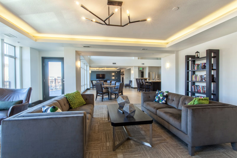 Luxury apartment community amenity space with large dark grey couches, modern lighting, and accents of olive green.