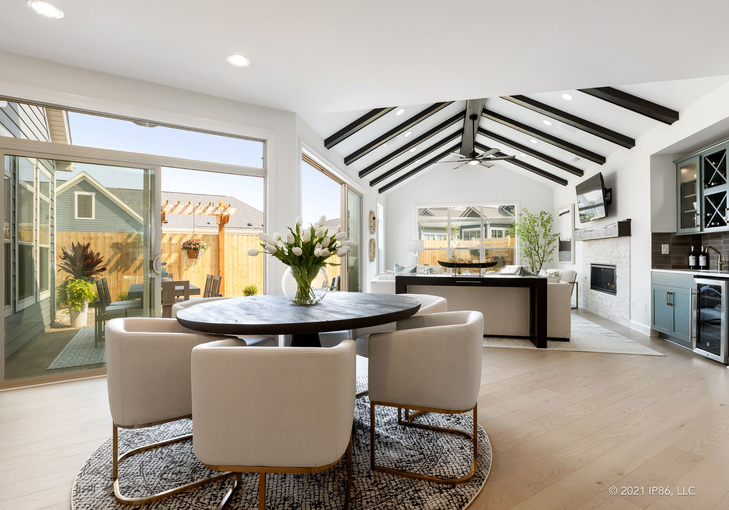 Dinning room looking onto beautiful great room with exposed beams and seamless indoor outdoor living.
