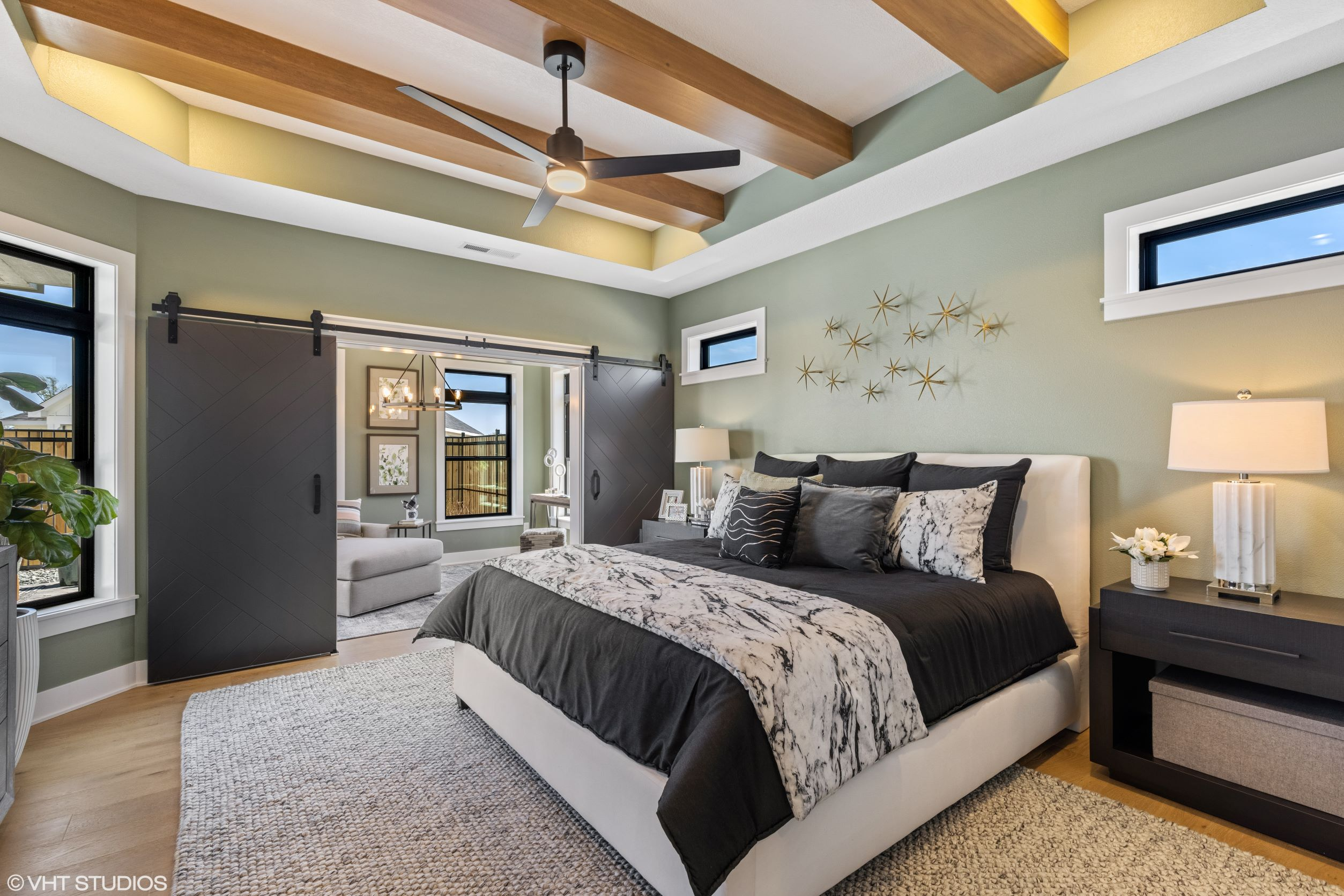 Sophisticated farmhouse model home owners suite with bonus seating room in view in Ames, IA.